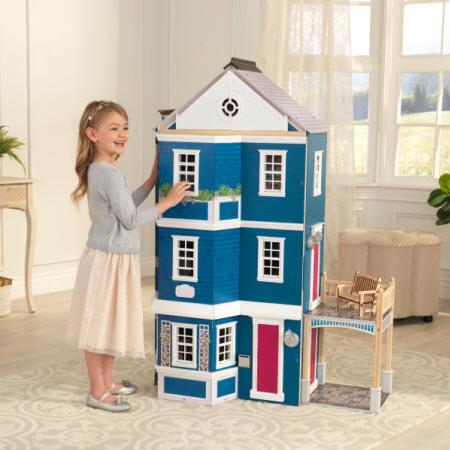 Niña posando feliz con su kidkraft casa gran aniversario 65947 width=