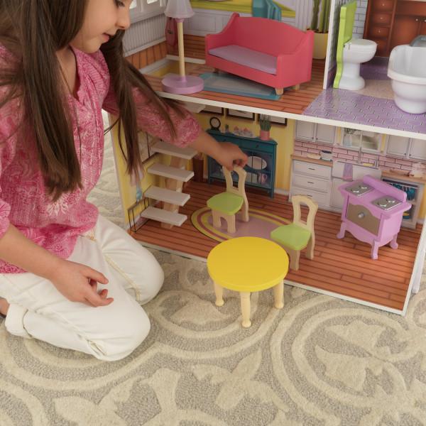 Detalle de niña jugando con sillas y mesa en la cocina de casa kidkraft de muñecas poppy 65959
