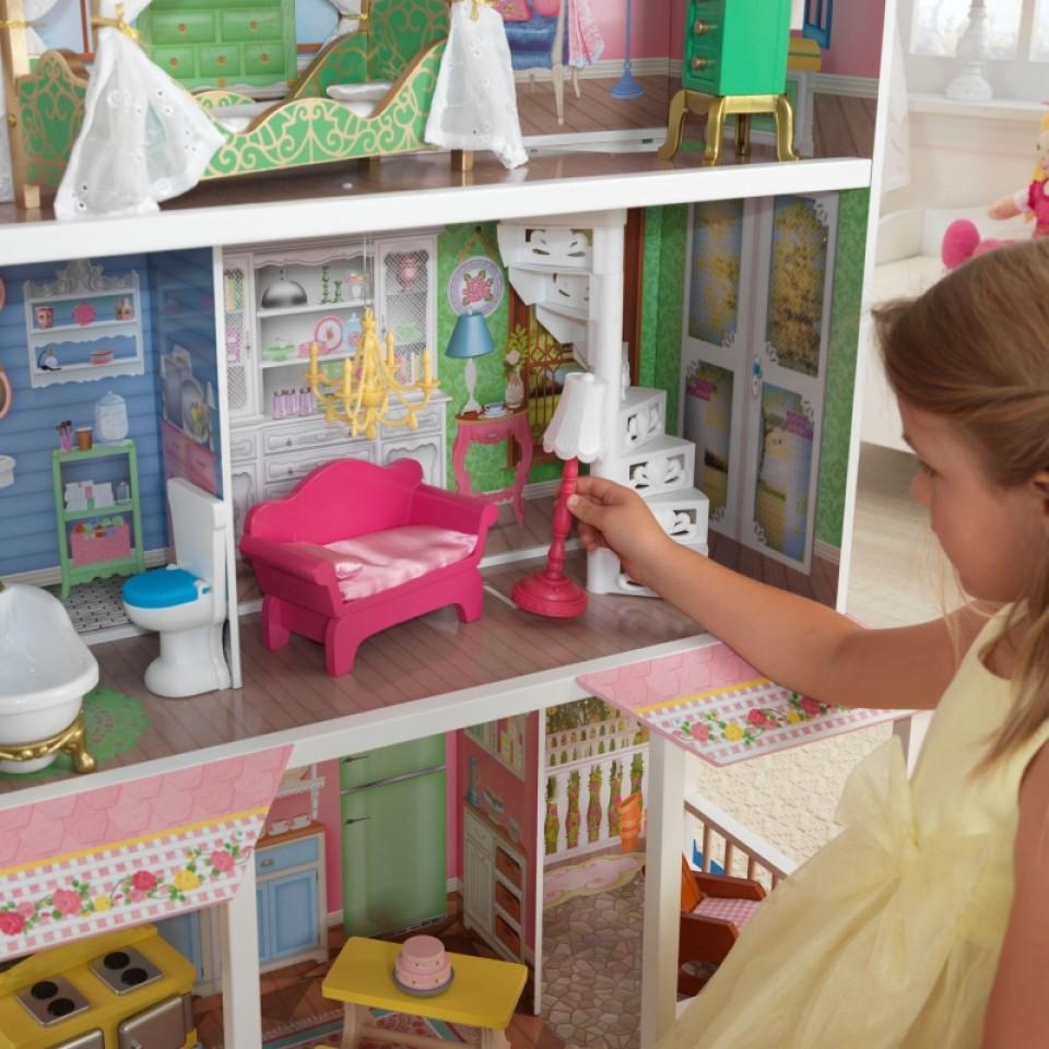 Niña colocando la lámpara en su Kidkraft casa de muñecas dulce savannah 65935 width=