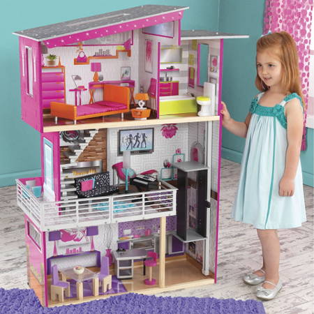 Niña posando con su Kidkraft casa de muñecas luxury 65871