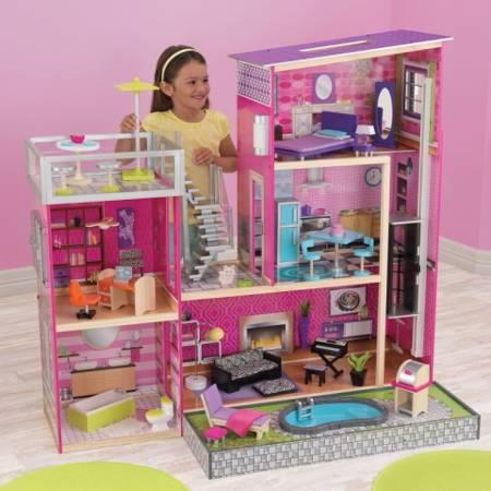 Niña jugando con su Kidkraft Casa De Muñecas Uptown 65833