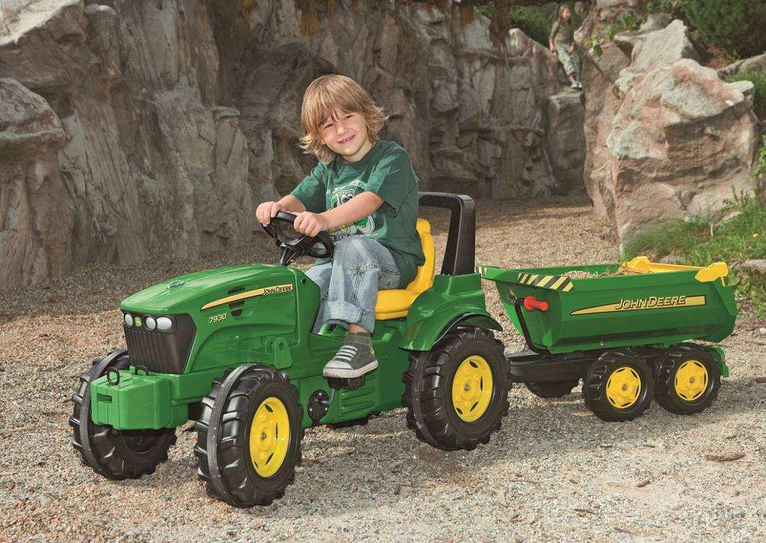 Niño jugando con su tractor de pedales John Deere 7930 y su remolque opcional width=