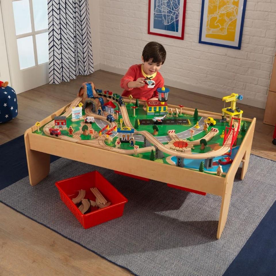 Niño jugando con su kidkraft juego de mesa de madera con circuito para trenes montaña y cascada 17850
