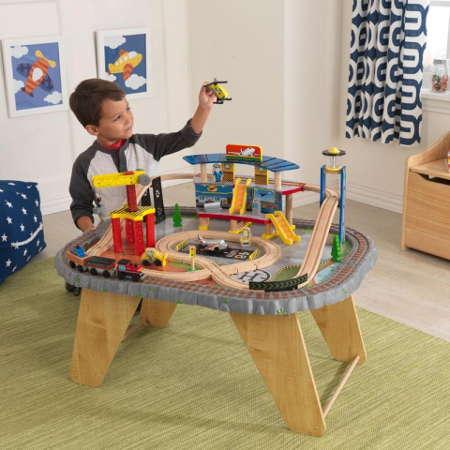 Niño jugando con su kidkraft set de trenes con mesa estacion de transportes 17564
