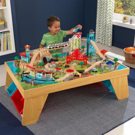 Niño jugando con su kidkraft set de trenes con mesa aerociudad 17554