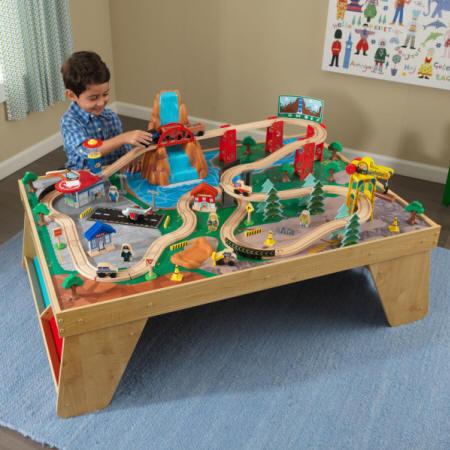 Niño con su kidkraft set de trenes con mesa estacion y cascada natural 18001
