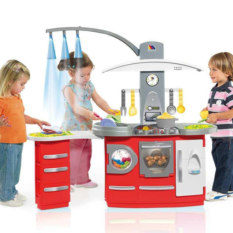 Cocina vista de frente con tres niños jugando y con la luces encendidas.